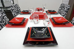 Glassware set on white table. Very nice combination of black and red glass, coloured plates, glasses for different types of dinks, all this is set on modern Royalty Free Stock Photos