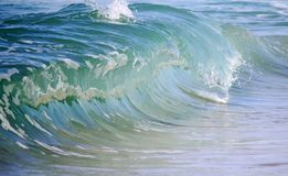 Glassy blue barreling wave. Photograph of a smooth glassy barreling beach break wave royalty free stock images