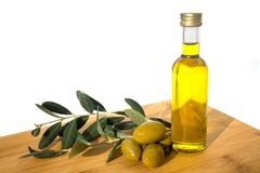 Glassy bottle of olive oil with group of green shiny olives and brunches with leafs royalty free stock image
