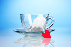 Glassy cup with saucer. And tea bag with red heart-shaped label on blue background stock image