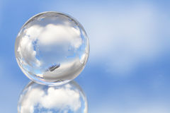 Glassy globe in sky. Close-up of nice glassy globe on background with blue sky and clouds royalty free stock images