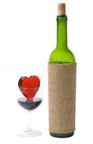 Glassy heart in a glass of wine and the bottle. Isolated at the white background Royalty Free Stock Photography