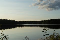 Glassy Lake Reflects the Summer Sky. A blue summer sky is reflected off of a glassy lake in New Hampshire royalty free stock image