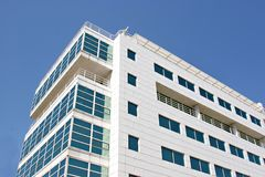 Glassy office building. Glass office building against a bright blue sky Royalty Free Stock Photos