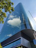 Glassy Skyscraper. A Glassy and shiny skyscraper building showing reflection of the cloud royalty free stock photography
