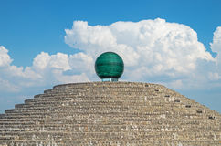 Glassy sphere. Large glass sphere on a mirrored pedestal and stone base royalty free stock photo