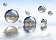 Glassy spheres floating on the water. Glassy spheres reflecting beautiful beach, floating on the water Stock Photo