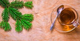 Glastasse tee auf einer alten rustikalen Tabelle mit Kiefernniederlassung Neuer Yea Stockfotos
