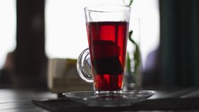 Glastasse tee mit dem Teebeutelinnere gesetzt auf Tabelle an der dunklen Restauranthalle stock footage