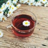 Glastasse tee mit einem Blumenstrauß von Gänseblümchen Lizenzfreies Stockfoto