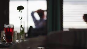 Glastasse tee mit kleinem Vase mit der Blume gesetzt auf Tabelle am dunklen Restaurant stock video