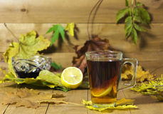 Glastasse tee, Stau und Zitrone auf einem Hintergrund einer hölzernen Brandung Lizenzfreie Stockfotos