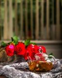 Glasteekanne auf einem dunklen Hintergrund Rote Rosen in der Nähe Stockfotografie