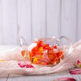 Glasteekanne mit Blumen auf einem hellen Hintergrund Lizenzfreie Stockfotografie