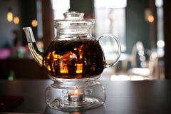 Glasteekanne mit dem Tee erhitzt mit Kerze Stockfotos