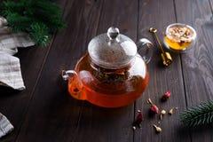 Glasteekanne mit frisch gebrautem Kräutertee und Honig auf einem hölzernen Hintergrund Weihnachten oder heißes Wintergetränk zum  stockfotografie