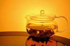 Glasteekanne mit Tee auf Glastisch Stockfoto