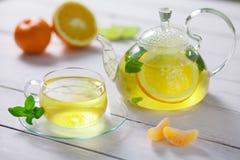 Glasteekanne und Schale mit grünem Tee, Orange, Mandarine, Kalkminze auf weißem Holztisch Stockfotografie