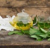 Glasteekanne und Schale mit Kräutertee Stockfotos