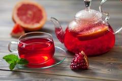 Glasteekanne und Schale roter Tee mit Traube, Granatapfel, Minze auf einem braunen Holztisch Stockfotografie