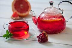 Glasteekanne und Schale roter Tee mit Traube, Granatapfel, Minze auf einem weißen Holztisch Lizenzfreies Stockbild