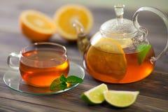 Glasteekanne und Schale schwarzer Tee mit Orange, Zitrone, Kalkminze auf einem Holztisch Lizenzfreies Stockbild