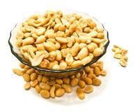 Glasteller mit geschmackvollen Erdnüssen stockfotografie