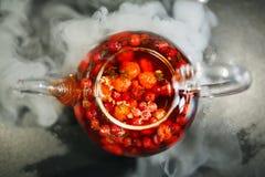 Glastheepot met bloemen en bessen, groene thee wordt gevuld die Smakelijke mooie drank in oranje tonen op een zwarte achtergrond  royalty-vrije stock fotografie