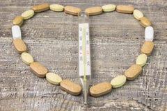 Glasthermometer, de tabletten van hartmedicijnen de houten lijst als achtergrond De mening vanaf de bovenkant royalty-vrije stock afbeelding
