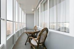 Glastisch- und Rattanweidensitzstuhl Weidenstühle des möbelrattantischs zwei nahe dem Fenster auf Balkon Stockfoto