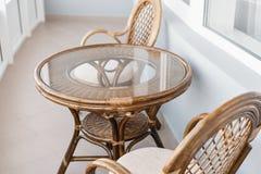 Glastisch- und Rattanweidensitzstuhl Weidenstühle des möbelrattantischs zwei nahe dem Fenster auf Balkon Lizenzfreie Stockfotos