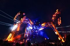"Glastonbury Arcadia stage night. Glastonbury, United Kingdom - June 29, 2014: Acrobats swing from the arms of a giant mechanical ""monster"" equipped with Royalty Free Stock Photography"