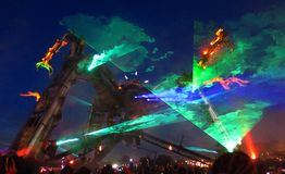 "Glastonbury Arcadia stage night. Glastonbury, United Kingdom - June 29, 2014: Acrobats swing from the arms of a giant mechanical ""monster"" equipped with Royalty Free Stock Image"