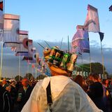 Glastonbury Festival beer hat festival fashion. Glastonbury, England - June 27, 2014: A man at Glastonbury Festival finds a creative use for his used beer cans Royalty Free Stock Images