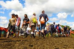 Glastonbury Festival crowds walk through mud beneath sunny sky. Glastonbury, United Kingdom - June 29, 2014: At Glastonbury Festival, England's most popular Royalty Free Stock Photography