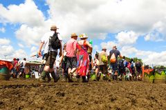 Glastonbury Festival crowds walk through mud beneath sunny sky. Glastonbury, United Kingdom - June 29, 2014: At Glastonbury Festival, England's most popular Royalty Free Stock Image