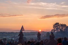 Glastonbury Festival. 30th June. 2014. A crowd watching the sunrise. With a couple silhouetted against the sun stock image
