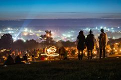 Glastonbury Festival. 30th June 2014. Three young woman looking across the lights and crowds of Glastonbury Festival at night. Wit royalty free stock images