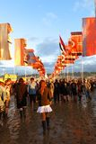 Glastonbury music festival crowds mud flags. Glastonbury, United Kingdom - June 27, 2014: Crowds trek through the mud beneath brightly colored flags after a Stock Photography
