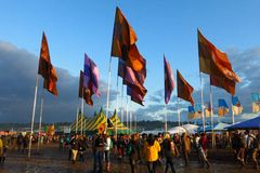 Glastonbury music festival crowds mud tents flags. Glastonbury, England - June 27, 2014: Crowds trek through the mud beneath brightly colored flags after a Stock Images