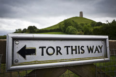 Glastonbury Tor This Way. Sign pointing the direction to Glastonbury Tor, Somerset, England. Selective focus on sign and St Michael's Tower out of focus in the Royalty Free Stock Photography