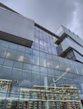 Glasvägg av modern kontorsbyggnad med reflexion av konstruktionsplatsen royaltyfri bild