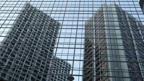Glasvägg med reflekterade byggnader arkivfoto