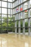 glasvägg, stålram och marmorgolv i modern kontorsbyggnadkorridor; fönsterväggen, övar påtryckningar i regeringsställning utrymme, royaltyfri foto