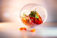 Glasvaas met rode roze bloemblaadjes wordt gevuld dat Het concept van Aromatherapy Stock Afbeeldingen