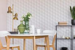 Glasvase mit Blumen auf weißem Holztisch mit Platte, Kaffeetassen und Gläsern, wirkliches Foto mit Kopienraum lizenzfreies stockfoto