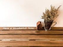 Glasvase mit Trockenblumen und Holzhaus auf Holztisch gegen weißen Hintergrund Stockbild