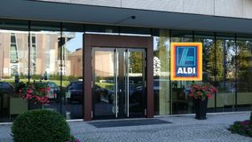 Glasvoorgevel van een modern bureaugebouw met Aldi-embleem Het redactie 3D teruggeven Royalty-vrije Stock Afbeelding