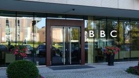 Glasvoorgevel van een modern bureaugebouw met het Britse embleem van het Omroepbbc Het redactie 3D teruggeven Royalty-vrije Stock Foto's