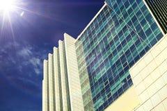 Glasvoorgevels van een wolkenkrabber in een heldere zonnige dag met zonnestraal stock fotografie